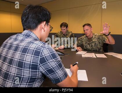 180830-N-FV739-006  CHANGI NAVAL BASE, SINGAPORE (August 30, 2018) - Rear Adm. Joey Tynch, commander, Task Force 73, explains the importance of maritime domain awareness during a media interview for Southeast Asia Cooperation and Training (SEACAT). This is the 17th annual SEACAT exercise and includes participants from the U.S., Brunei, Bangladesh, Thailand, Philippines, Singapore, Vietnam, Malaysia and Indonesia. (U.S. Navy photo by Mass Communication Specialist 3rd Class Christopher A. Veloicaza) - Stock Image