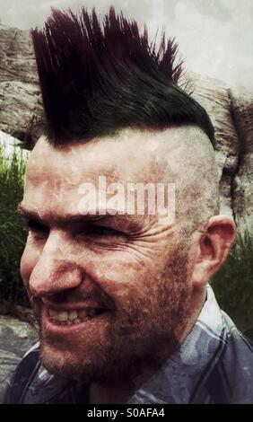 Smiling, middle aged man with a mohawk hairdo. - Stock Image