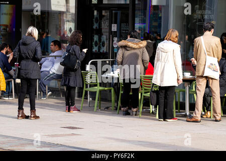 A group of people gathered together outside the Costa coffee shop drinking coffee chatting to one another in Dundee, UK - Stock Image