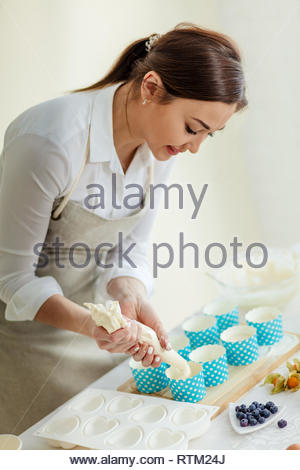 woman poring dough in the decorative cupcake liners, close up side view photo. - Stock Image