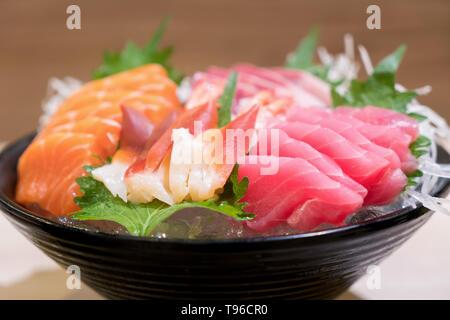 Mixed sliced fish sashimi on ice in black bowl. Sashimi Salmon Tuna Hamachi Prawn and Surf Calm set, raw fish, japanese food in Asian restaurant. - Stock Image