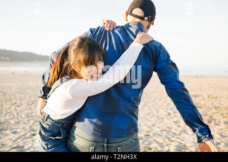 Father carrying on the back his funny daughter on the beach in a sunny day - Stock Image