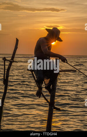 Stick Fishermen at sunset near Tangalle, in the southern coast of Sri Lanka - Stock Image