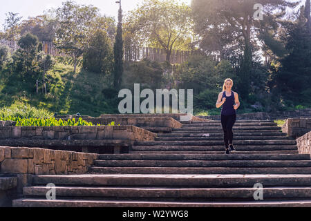 young sporty woman running downstairs in the morning on the stairs of the park, morning workout outdoors, sports and healthy lifestyle - Stock Image