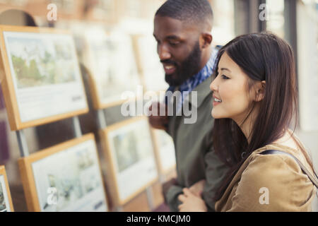 Smiling young couple looking at real estate listings at storefront - Stock Image