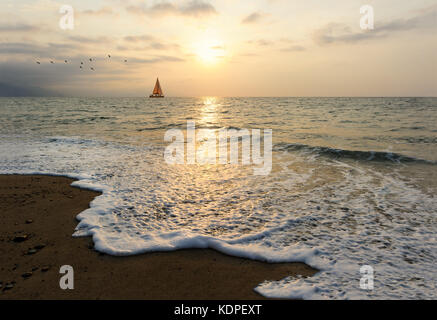 Sunset sailboat is a sailboat sailing along the ocean at sunset. - Stock Image