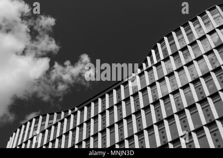Black and white image looking up at a curvy roof of a modern city building in London - Stock Image