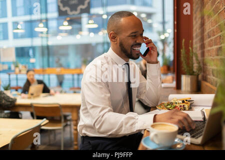 Smiling businessman talking on smart phone, working in cafe - Stock Image