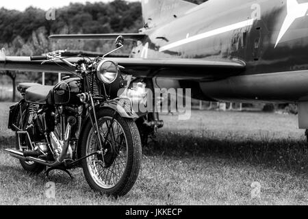 Old, black motorcycle made by Triumph Motorcycles - british brand with an airplane in the background. Black and - Stock Image
