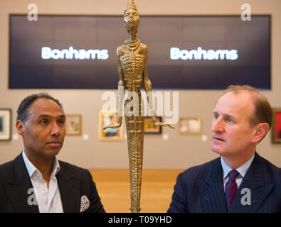 Bonhams, New Bond Street, London, UK. 18 March, 2019. Leading Bonhams Modern and Contemporary African Art sale, which takes place on 20 March 2019, are works by Benedict Chukwukadibia Enwonwu and Gerard Sekoto. Costume Designer and Creative Director Roubi L'Roubi (left) has curated a section of the African Art sale, seen here with Giles Peppiatt (right), Director, Modern & Contemporary African Art, Bonhams, viewing Ben Enwonwu's sculpture, Anyanwu, which has an estimate of £100,000-150,000. Credit: Malcolm Park/Alamy Live News. - Stock Image