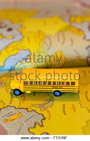 Toy classic yellow school bus on a European map from a atlas book in soft focus on circa June 2019 in Poznan, Poland. - Stock Image