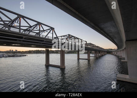 The dual new and old Iron Cove Bridges that join the Sydney suburbs of Drummoyne and Rozelle over the upper reaches of Sydney Harbour. - Stock Image