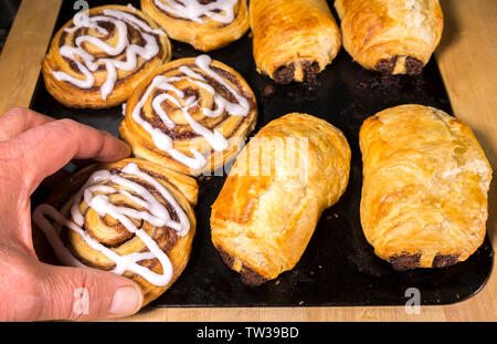 Man's hand in closeup choosing a hot, flakey pastry from a baking tray, fresh from the oven. - Stock Image