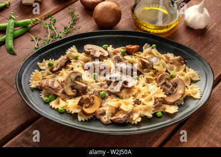 Mushroom pasta with ingredients on a dark rustic wooden background - Stock Image