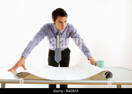 Asian business man standing looking over blueprints - Stock Image