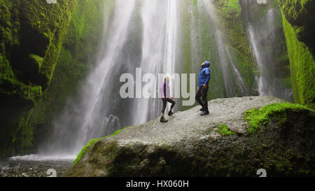 Low angle view of couple standing on mossy boulder admiring waterfall in remote landscape - Stock Image