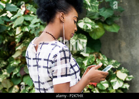 portrait of young businesswoman standing outside and making messages - Stock Image