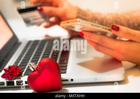 Woman shopping online during christmas holiday with credit card and smart phone - Stock Image