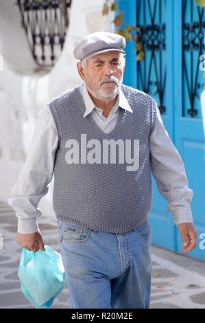 Older Greek man walking on a street of Parikia in the island of Paros. - Stock Image