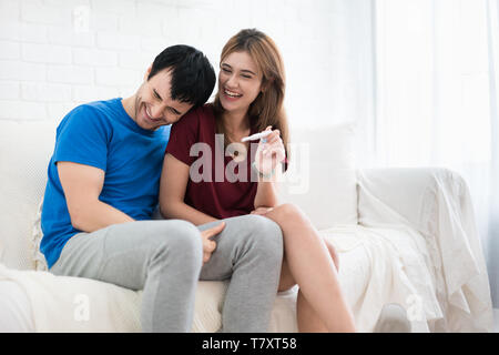 Closeup of happy young woman embracing man after positive pregnancy test sitting besides husband in room - Stock Image
