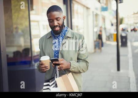 Young man with coffee and shopping bags texting with cell phone on urban sidewalk - Stock Image