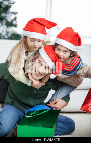 Father Piggybacking Children During Christmas - Stock Image