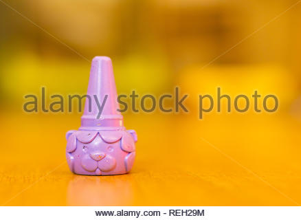 Poznan, Poland - October 10, 2018: Purple lion shaped crayon on a wooden floor in soft focus background - Stock Image