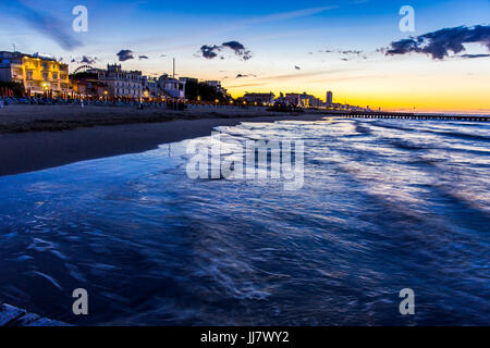 View at the beach and hotels from pier at sunrise. Jesolo beach, Italy. - Stock Image