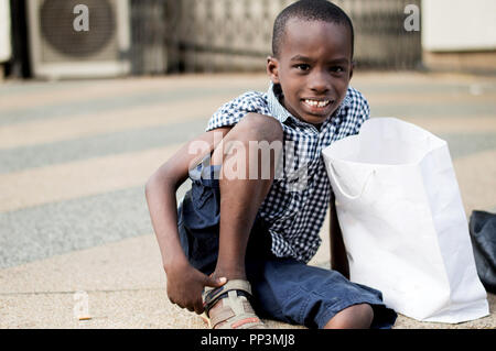 Little boy sitting next to his mother's shopping bag and smiling at the camera. - Stock Image