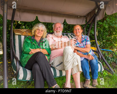 Three friends on garden swing seat - France. - Stock Image