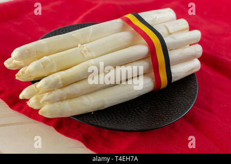 New harvest of white asparagus vegetable, high quality Belgian asparagus with ribbon in colors of Belgian flag close up - Stock Image