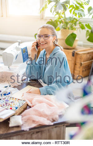 Young female fashion designer in blue elegant blouse looking at camera while taking the order, discussing bespoke party dress with customer by phone - Stock Image