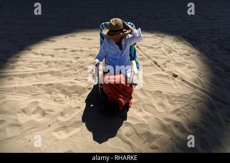 Woman on the beach in a circle of light, Condado, San Juan, Puerto Rico - Stock Image