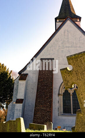 St Mary The virgin church in Northolt Village, Middlesex, United Kingdom behind the edge of a gravestone - Stock Image