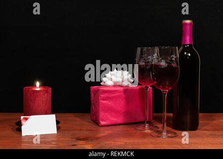 Beautiful etched wine glasses and bottle of red wine, red candle, wrapped present with bow on wooden table with name tag on dark background. Valentine - Stock Image