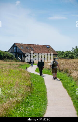 People walking on path between cliffs and Visitor Centre Center at Bempton Cliffs RSPB Reserve, UK. - Stock Image