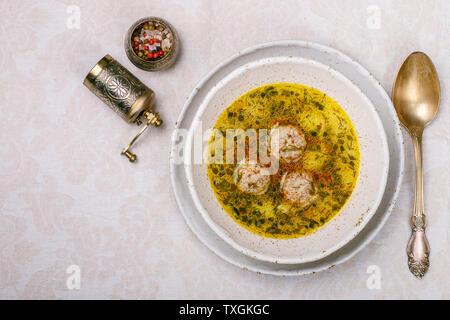 Delicious soup with chicken or Turkey meatballs with vegetables - potatoes, carrots, dill, parsley and spices in a white plate. Selective focus, top v - Stock Image