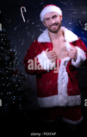 Handsome smiling male santa with beard pulls open his jacket to reveal chest with Christmas tree in background - Stock Image