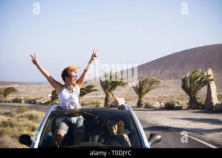 Couple of happy woman enjoy the trip traveling by car - driving and standing outside the roof with success and happiness pose - vacation in outdoor tr - Stock Image