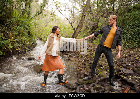 Woman helping man across creek. - Stock Image