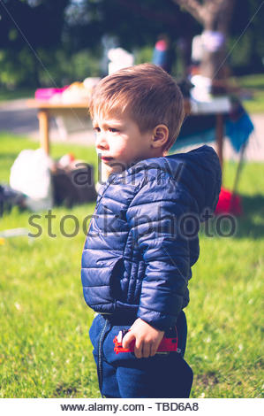 Young boy with blue jacket holding a red plastic - Stock Image