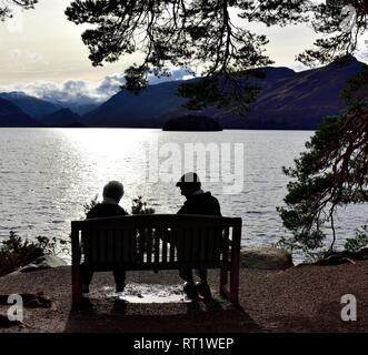 Pensioner couple sitting on a bench in front of Derwent water,Keswick,Lake District,Cumbria ,England,UK - Stock Image