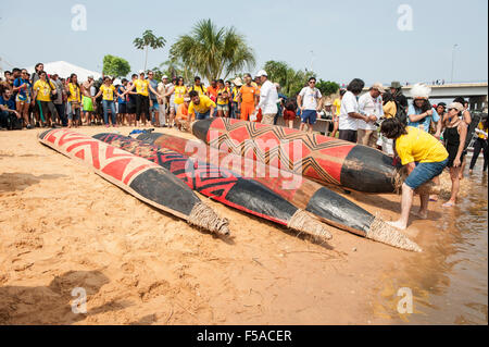 Brightly painted canoes with traditional tribal designs lie on the beach before the canoeing event at the International - Stock Image