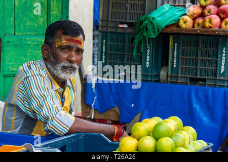 A bearded man with a tilaka in a street market selling lemons and fruit - Stock Image