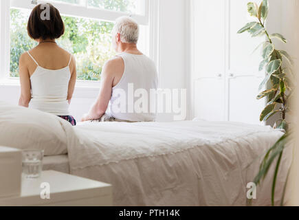 Thoughtful senior couple sitting on bed looking out window - Stock Image