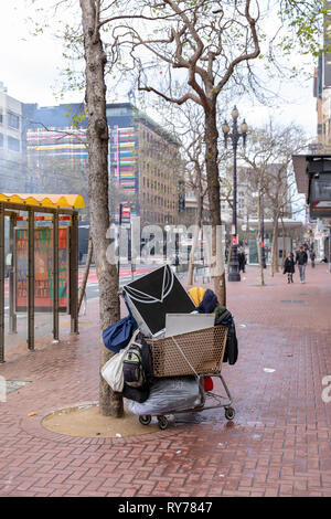 Homeless person's belongings in shopping trolley on pavement; Market Street, San Francisco, USA - Stock Image