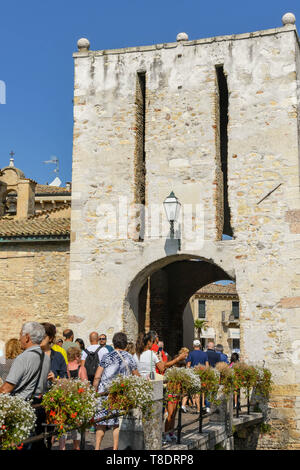 SIRMIONE, LAKE GARDA, ITALY - SEPTEMBER 2018: People crossing a bridge to enter the old town and Scaliger Castle. It is a medieval fortress in the lak - Stock Image