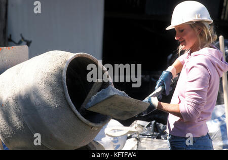 young female labourer on building site filling up cement mixer - Stock Image