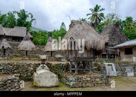 Catholic tomb next to thatched structures symbolising female and male ancestors, Luba hamlet, Ngada District, Island of Flores, Indonesia. - Stock Image