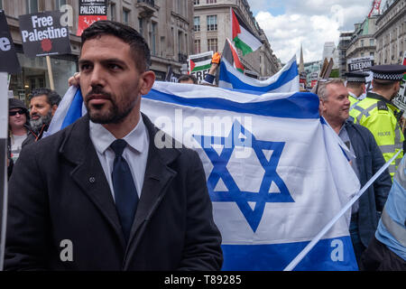London, UK. 11th May 2019. A small group with Israeli flags shout at marchers from the BBC to a rally in Whitehall a few days before Nakba day showing solidarity with the Palestinian people and opposing continued Israel violation of international law and human rights. The protest called for an end to Israeli oppression and the siege of Gaza and for a just peace that recognises Palestinian rights including the right of return. It urged everyone to boycott and divest from Israel and donate to medical aid for Palestine. Peter Marshall/Alamy Live News Credit: Peter Marshall/Alamy Live News - Stock Image